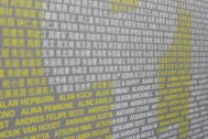 Runners from around the world, look for their name on the wall of registered participants.